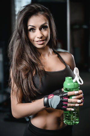 Beautiful sexy athletic young brunette Caucasian girl taking protein sports nutrition in the gym and poses fitness and bodybuilding concept