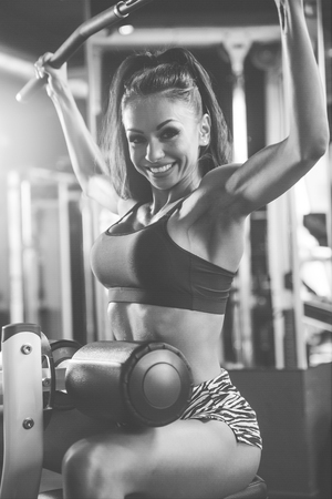 Beautiful sexy athletic young brunette Caucasian girl working out training pumping up back lats muscles in the gym gaining weight on machines posing fitness and bodybuilding concept Standard-Bild