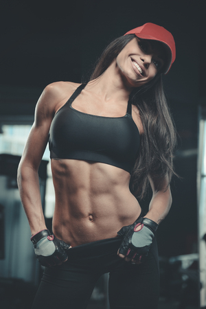 Beautiful sexy athletic young brunette Caucasian girl working out training in the gym gaining weight pumping up muscles and poses fitness and bodybuilding concept