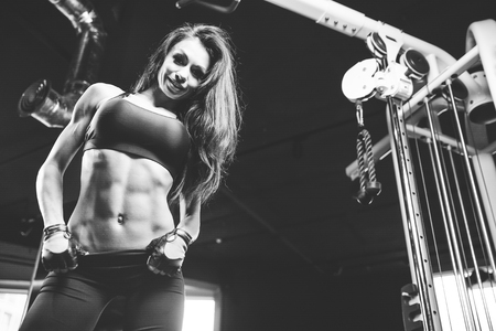 Beautiful sexy athletic young brunette Caucasian girl working out training pumping up abdominal muscles abs sixpacks in the gym on machines gaining weight and poses fitness and bodybuilding concept Standard-Bild