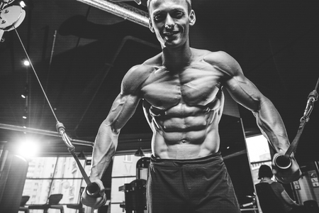 Brutal handsome Caucasian bodybuilder working out in the gym training chest pumping up pectoral muscles withdumbbells and on crossovers gaining weight and poses fitness and bodybuilding concept Foto de archivo - 96207057