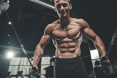 Brutal culturista caucásico guapo ejercitándose en el pecho de entrenamiento de gimnasio bombeando músculos pectorales con pesas y cruces para aumentar de peso y plantea concepto de fitness y culturismo Foto de archivo