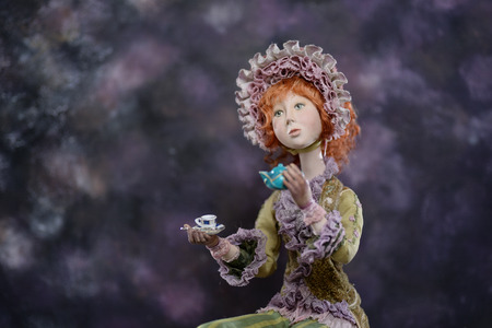Porcelain paper mache clay statuette girl pretty woman young girl dress redhead beauty handmade handcrafted toy craft vintage silk bonnet hat cap teacup cup tea teapot decor doll gift texture concept Stock Photo