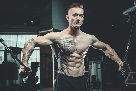 Brutal handsome Caucasian bodybuilder working out in the gym training chest pumping up pectoral muscles with dumbbells and on crossovers gaining weight Stock Photo