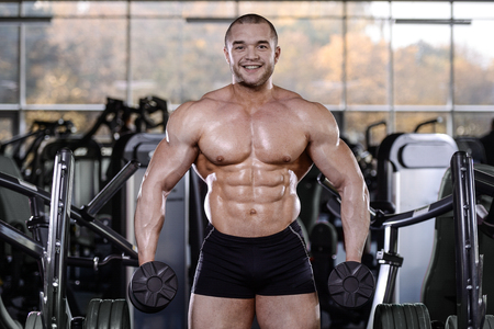 Brutal strong bodybuilder athletic fitness man pumping up abs muscles workout bodybuilding concept background