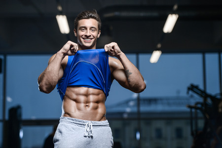 Handsome young fit muscular caucasian man of model appearance workout training in the gym Banco de Imagens