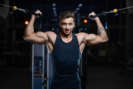Handsome young fit muscular caucasian man of model appearance workout training in the gym gaining weight Stock Photo