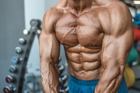 Brutal strong bodybuilder athletic aged man pumping up muscles workout bodybuilding concept background - muscular bodybuilder handsome men doing exercises in gym naked torso sport and diet concept