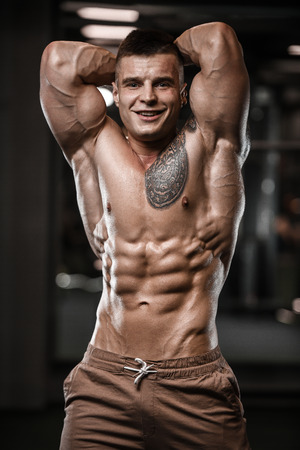Handsome strong bodybuilder athletic man pumping up muscles workout bodybuilding concept background - muscular bodybuilder handsome men doing exercises in gym naked torso sport and diet concept Banque d'images