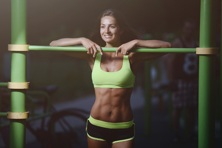 outdoor sport Beautiful strong athletic muscular young caucasian fitness woman workout training in the gym on diet pumping up abs muscles and posing bodybuilding health care and fitness body bar concept