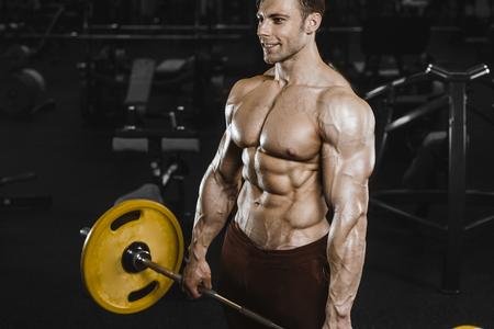 Handsome strong athletic men pumping up muscles workout bodybuilding concept background - muscular bodybuilder handsome men doing exercises in gym naked torso Standard-Bild - 117420505