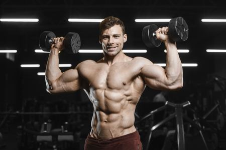 Handsome strong athletic men pumping up muscles workout bodybuilding concept background - muscular bodybuilder handsome men doing exercises in gym naked torso Standard-Bild - 117420515
