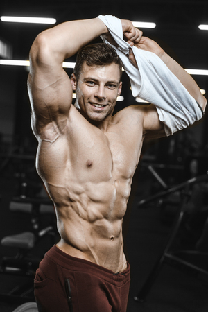 Handsome strong athletic men pumping up muscles workout bodybuilding concept background - muscular bodybuilder handsome men doing exercises in gym naked torso Standard-Bild - 117420517