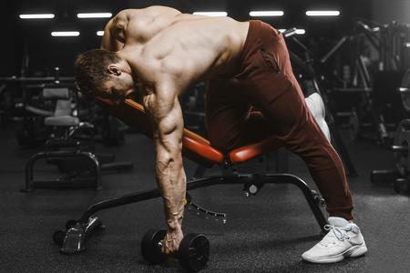 Handsome strong athletic men pumping up muscles workout bodybuilding concept background - muscular bodybuilder handsome men doing exercises in gym naked torso Standard-Bild - 117420518