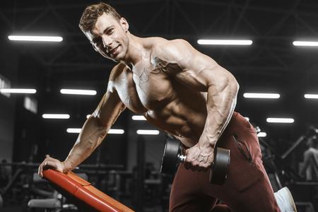 Handsome strong athletic men pumping up muscles workout bodybuilding concept background - muscular bodybuilder handsome men doing exercises in gym naked torso Standard-Bild - 117420523