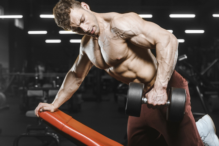 Handsome strong athletic men pumping up muscles workout bodybuilding concept background - muscular bodybuilder handsome men doing exercises in gym naked torso Standard-Bild - 117421348