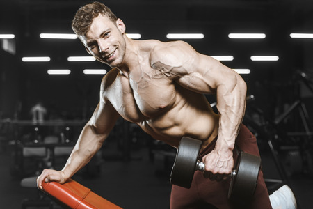 Handsome strong athletic men pumping up muscles workout bodybuilding concept background - muscular bodybuilder handsome men doing exercises in gym naked torso Standard-Bild - 117421350
