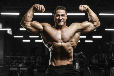 Handsome strong athletic men pumping up muscles workout bodybuilding concept background - muscular bodybuilder handsome men doing exercises in gym naked torso Standard-Bild - 118552409