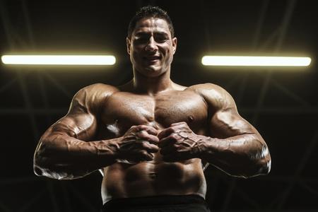 Handsome strong athletic men pumping up muscles workout bodybuilding concept background - muscular bodybuilder handsome men doing exercises in gym naked torso Standard-Bild - 118552585