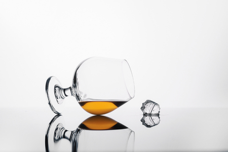 glass with cognac or whiskey on a white background and a cube of ice Stock Photo