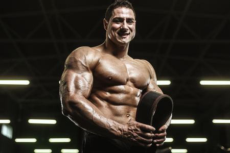 Handsome strong athletic men pumping up muscles workout bodybuilding concept background - muscular bodybuilder handsome men doing exercises in gym naked torso Standard-Bild - 118552601