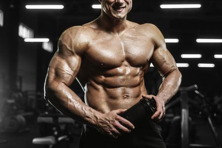 Handsome strong athletic men pumping up muscles workout bodybuilding concept background - muscular bodybuilder handsome men doing exercises in gym naked torso Standard-Bild - 118552534
