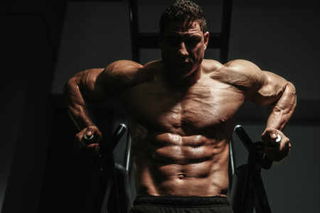 Handsome strong athletic men pumping up muscles workout push ups on bars bodybuilding concept background - muscular bodybuilder men doing exercises in gym naked torso Standard-Bild - 118552542