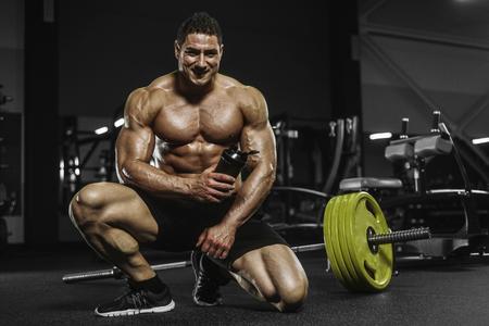 Handsome strong athletic men pumping up muscles workout bodybuilding concept background - muscular bodybuilder handsome men doing exercises in gym naked torso Standard-Bild - 118552545