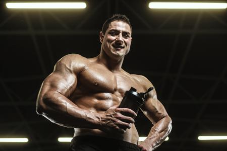 Handsome strong athletic men pumping up muscles workout bodybuilding concept background - muscular bodybuilder handsome men doing exercises in gym naked torso Standard-Bild - 118552578