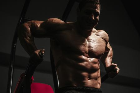 Handsome strong athletic men pumping up muscles workout push ups on bars bodybuilding concept background - muscular bodybuilder men doing exercises in gym naked torso Standard-Bild - 118552483