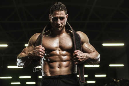Handsome strong athletic men pumping up muscles workout bodybuilding concept background - muscular bodybuilder handsome men doing exercises in gym naked torso Standard-Bild - 118552480