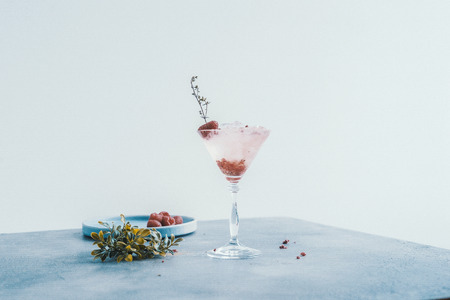 martini glass on a white background with an raspberries
