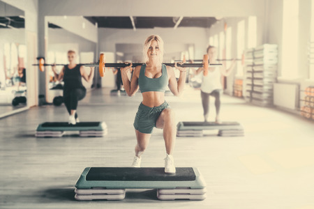 Beautiful strong sexy athletic muscular young caucasian fitness woman workout training in the gym on diet pumping up abs muscles and posing bodybuilding health care and fitness body bar concept