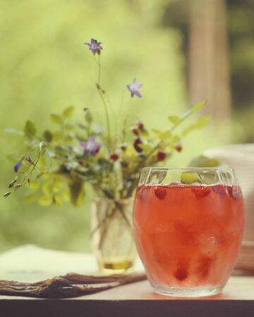 strawberry cocktail in a glass cup on the windowsill veranda summer day with a bouquet of flowers Forest landscape mood outdoor raw organic diet food Banco de Imagens