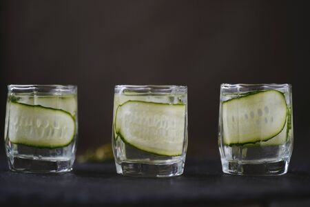 Vodka in shot glasses with cucomber pickles  on rustic wood background Banco de Imagens