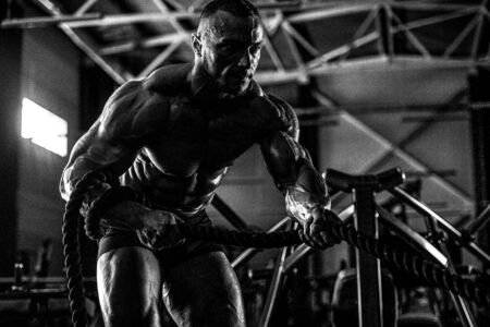 Handsome strong athletic men pumping up biceps muscles workout fitness and bodybuilding concept background - muscular bodybuilder fitness men doing arms exercises in gym naked torso
