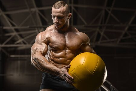 Handsome athletic men pumping up muscles workout with ball fitness exercises and bodybuilding concept background - muscular bodybuilder fitness men doing ball exercises in gym naked torso Banco de Imagens