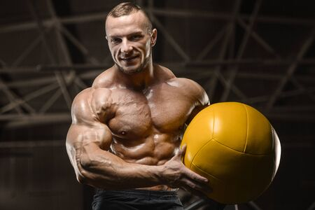 Handsome athletic men pumping up muscles workout with ball fitness exercises and bodybuilding concept background - muscular bodybuilder fitness men doing ball exercises in gym naked torso Banque d'images
