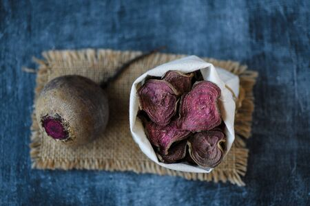 vegetarian pile of healthy beet chips Purple Baked Beet Chips Vegan snacks, vegetable chips in canvas bag and ceramic bowl, rustic still life, selective focus