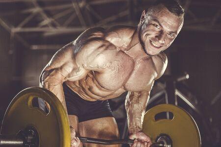 Brutal strong athletic men pumping up muscles workout bodybuilding concept background - muscular bodybuilder handsome men doing exercises in gym naked torso Banque d'images