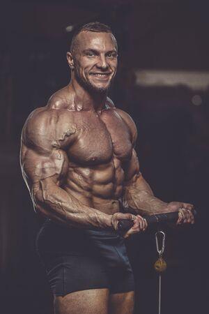 Brutal strong athletic men pumping up muscles workout bodybuilding concept background - muscular bodybuilder handsome men doing exercises in gym naked torso Banco de Imagens