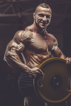 Brutal strong athletic men pumping up muscles workout bodybuilding concept background - muscular bodybuilder handsome men doing exercises in gym naked torso Banco de Imagens