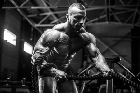 Brutale sterke atletische mannen oppompen van spieren training bodybuilding concept achtergrond - gespierde bodybuilder knappe mannen doen oefeningen in sportschool torso Stockfoto