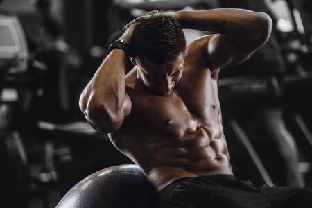 Handsome strong athletic men pumping up muscles workout fitness and bodybuilding concept background - muscular bodybuilder fitness men doing abs exercises in gym naked torso Banco de Imagens