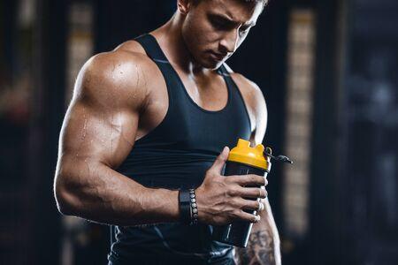 Sport muskulöser Fitness-Mann trinkt Wasser nach dem Training Cross-Fitness- und Bodybuilding-Konzept Gymnastikhintergrund abs-Muskelübungen im Fitnessstudio-Torso-Fitness-Konzept Standard-Bild