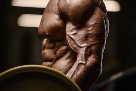 Hübscher starker athletischer Mann, der Bizepsmuskeln aufpumpt, trainiert Fitness- und Bodybuilding-Konzepthintergrund - muskulöse Bodybuilder-Fitness-Männer, die Armübungen im Gymnastiktorso machen