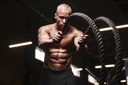 fitness athletes training using battle ropes intense workout team exercise challenge in gym enjoying healthy bodybuilding endurance practice lifestyle together Stockfoto