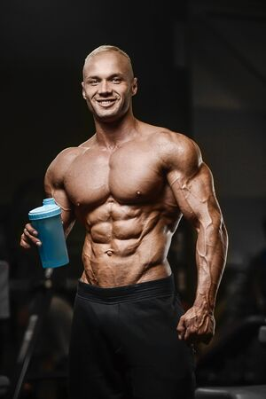 Sport muscular fitness man drinking water after workout cross fitness and bodybuilding concept gym background abs muscle exercises in gym naked torso fitness concept