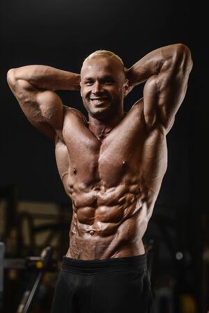 Hombres atléticos fuertes guapos bombeo de los músculos entrenamiento fitness y culturismo concepto de fondo - hombre de fitness culturista muscular haciendo ejercicios de abs en el torso de gimnasio