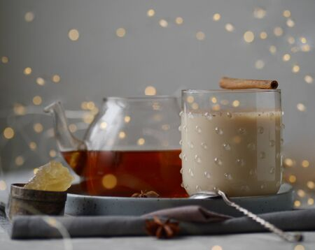 Masala warm spicy tea Indian chai warming drink with spice healthy food conception health new year Christmas decoration festoon shining glowing garland winter holidays treat ingredients components Stockfoto